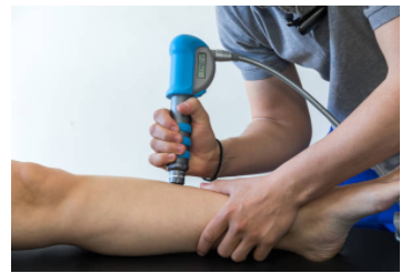 A practitioner performs shockwave to a client's leg
