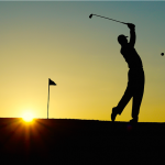 Shadow of golfer hitting ball with sunset behind