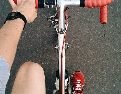 a hand reaches towards the handle bars of a bike